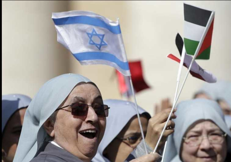 Nuns wave Israeli and Palestinian flags before Pope Francis