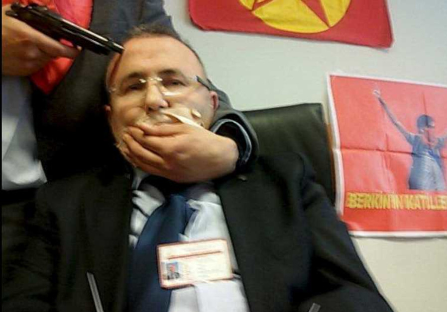 A gunman poses with prosecutor Mehmet Selim Kiraz with a gun on his head after he was taken hostage