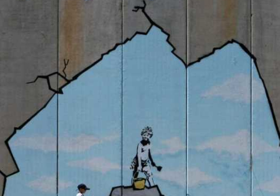 A Palestinian boy walks past a drawing by British graffiti artist Banksy