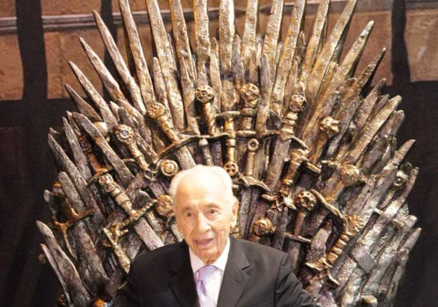 Former president Shimon Peres sits on a replica throne from the hit show 'Game of Thrones'