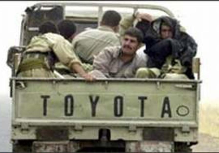 kurdish militia ride in truck