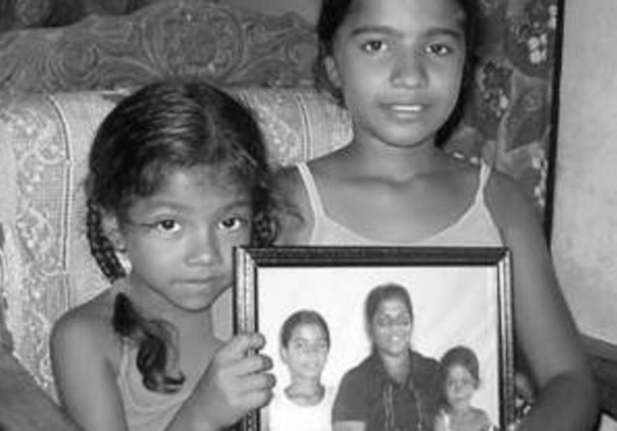 Sri Lankan orphans display a photo of their family