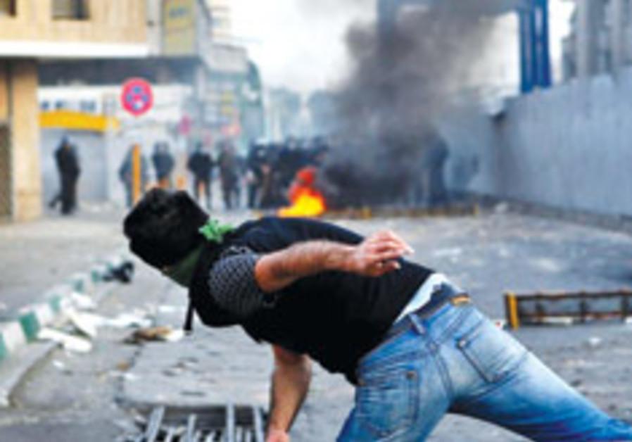 Iran protestor throws stone