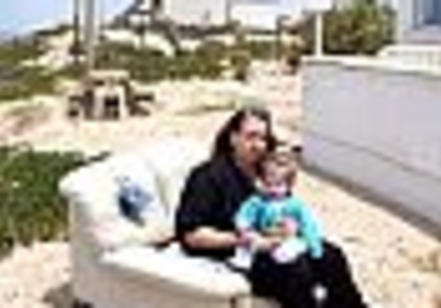 settler holds baby while sitting on couch outdoors
