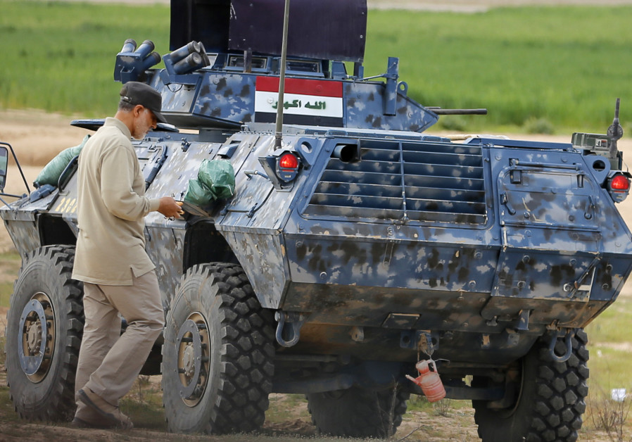 Iranian Revolutionary Guard Commander Qassem Soleimani walks near an armored vehicle at the frontline during offensive operations against Islamic State militants in Iraq