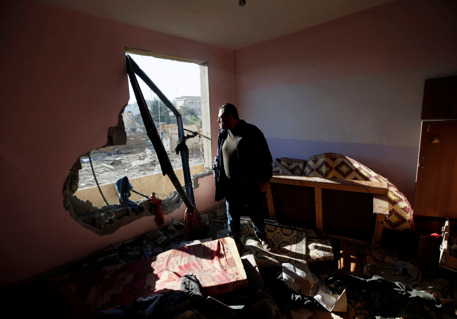 A Palestinian man looks at a nearby militant target in his apartment that was damaged in an Israeli airstrike, in the northern Gaza Strip December 9, 2017. MOHAMMED SALEM/ REUTERS