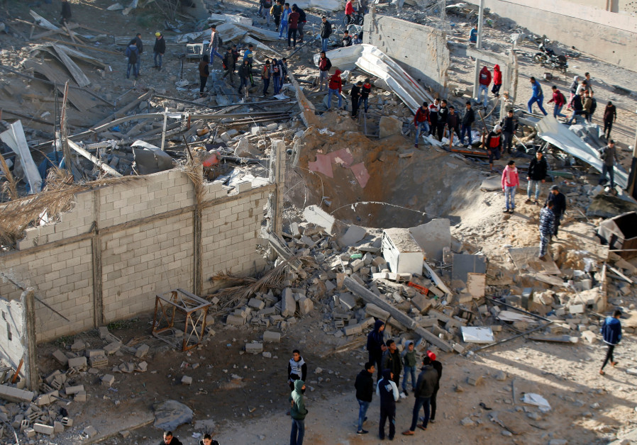 Palestinians gather around a militant target that was hit in an Israeli airstrike (credit: Mohammed Salem/ Reuters)