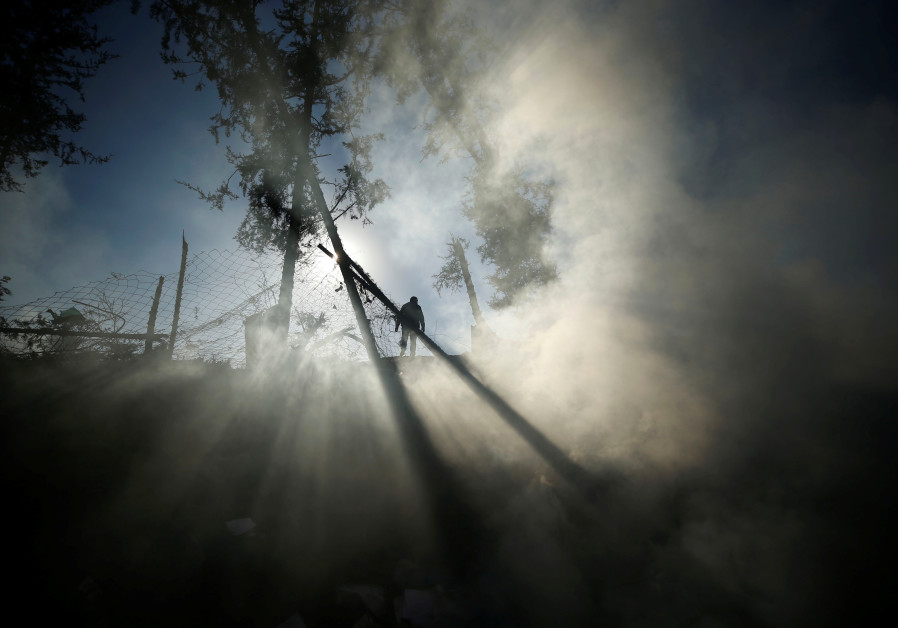 Smoke is seen as a Palestinian man inspects a militant target that was hit in an Israeli airstrike in the northern Gaza Strip  MOHAMMED SALEM/ REUTERS
