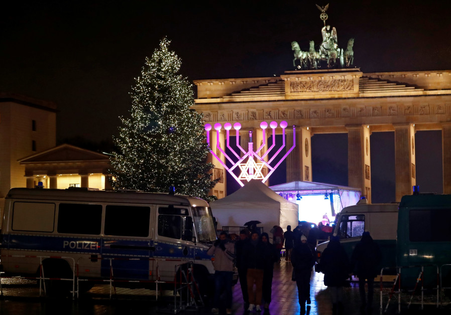 Europe's largest Hanukkah menorah is seen next to a Christmas tree during the lighting ceremony at the Brandenburg Gate in Berlin, Germany, December 12, 2017. / FABRIZIO BENSCH / REUTERS