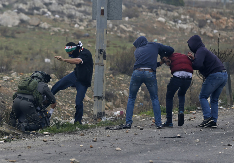 An undercover Israeli security personnel kicks a Palestinian while an Israeli soldier holds him down at a riot near Ramallah, December 2017 (credit: Abbas Momani/ AFP)