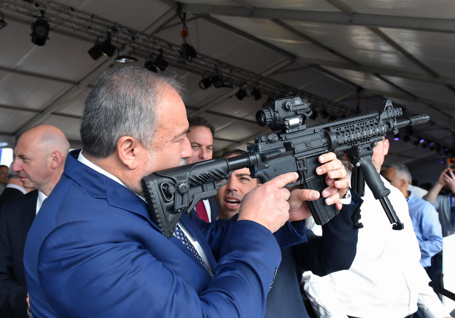 Defense Minister Avigdor Liberman holds a weapon during a visit to Sderot.  ARIEL HERMONI / DEFENSE MINISTRY
