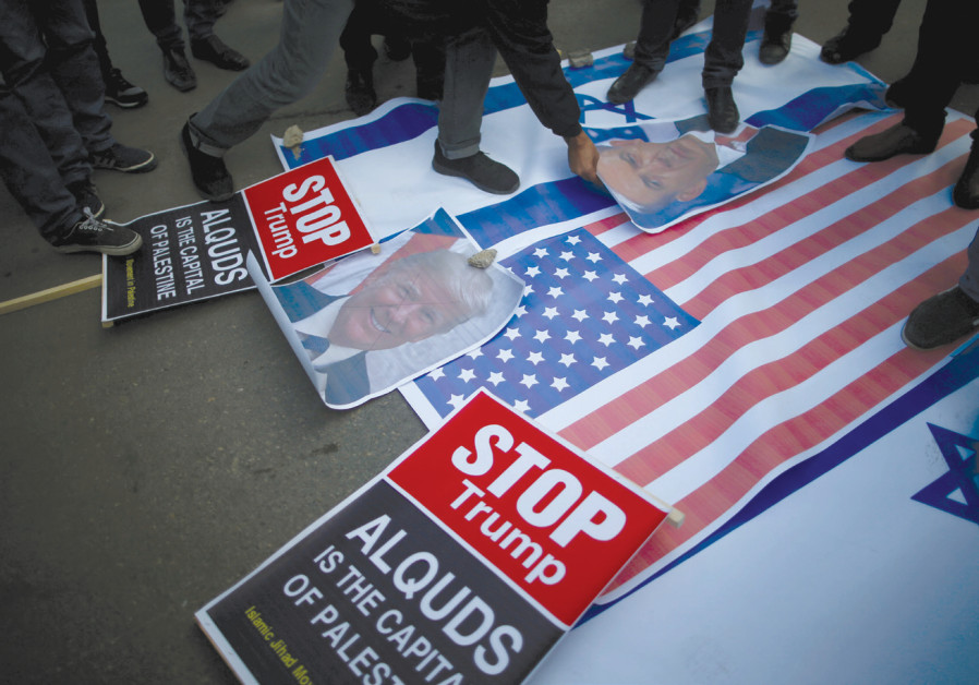 PROTESTERS IN Gaza City begin stomping on posters depicting Prime Minister Benjamin Netanyahu and US President Donald Trump and Israeli and American flags before burning them during a protest following Trump's recognition of Jerusalem as the capital of Israel /MOHAMMED SALEM/REUTERS