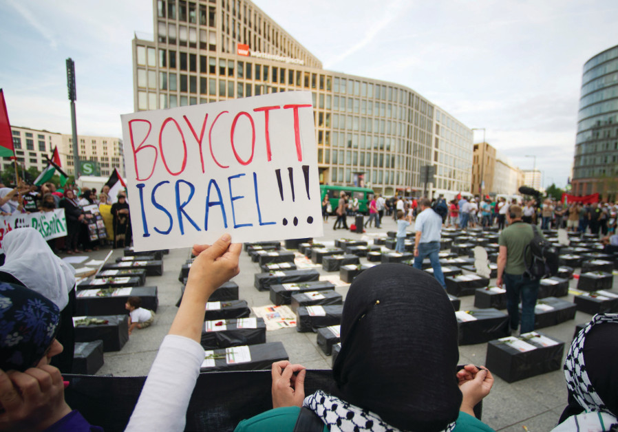 A WOMAN holds a 'Boycott Israel' sign in front of symbolic cof ns while attending a demonstration in 2014 supporting Palestine, in Berlin.