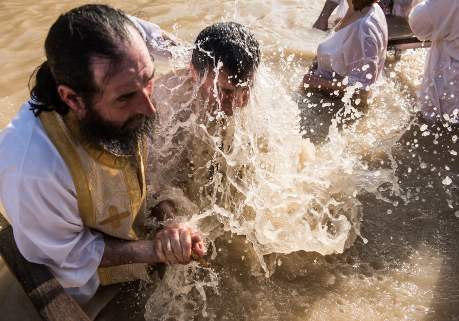 Christian Orthodox pilgrims during a traditional immersion ceremony, celebrate Epiphany holiday at Qasr el Yahud