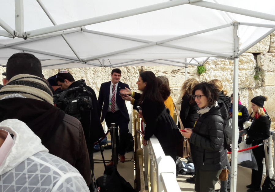 Female journalists are positioned behind a barrier in order to maintain Jewish traidtion of gender segregation.