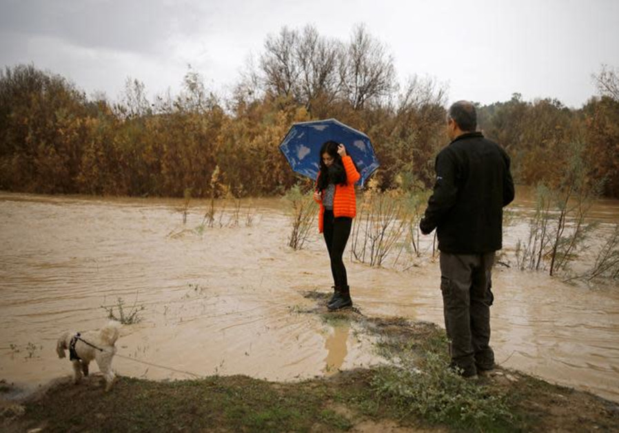 A girl poses for a photo on a riverbank of the flooded Besor stream on a rainy day, near Kibbutz Tze'elim at the Negev desert, Israel January 6, 2018. REUTERS/Amir Cohen