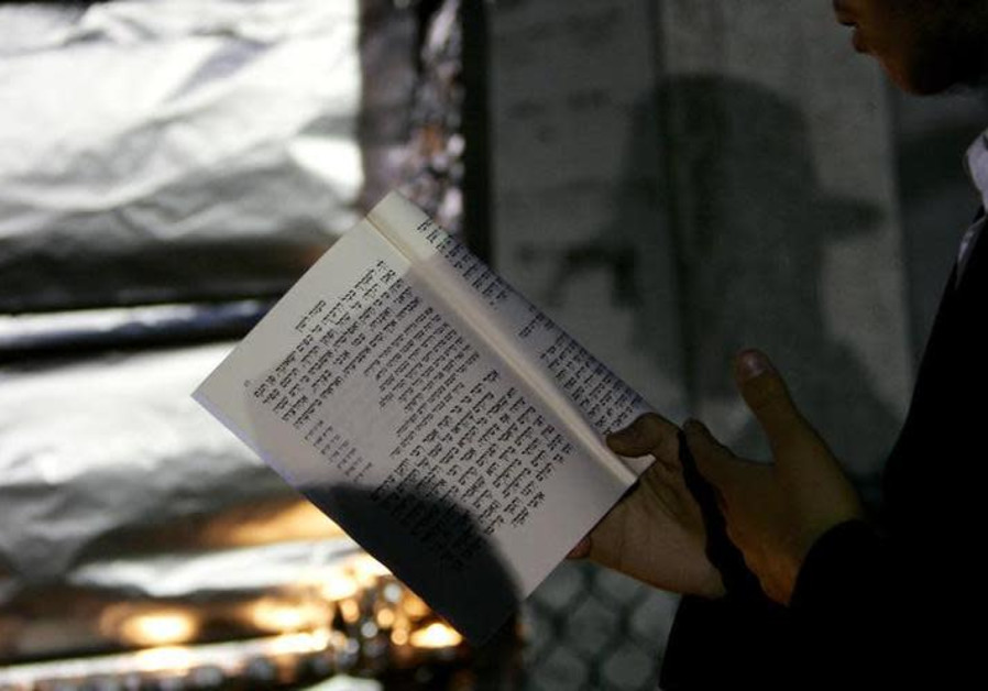 A man reads a prayer book outside, Reuters