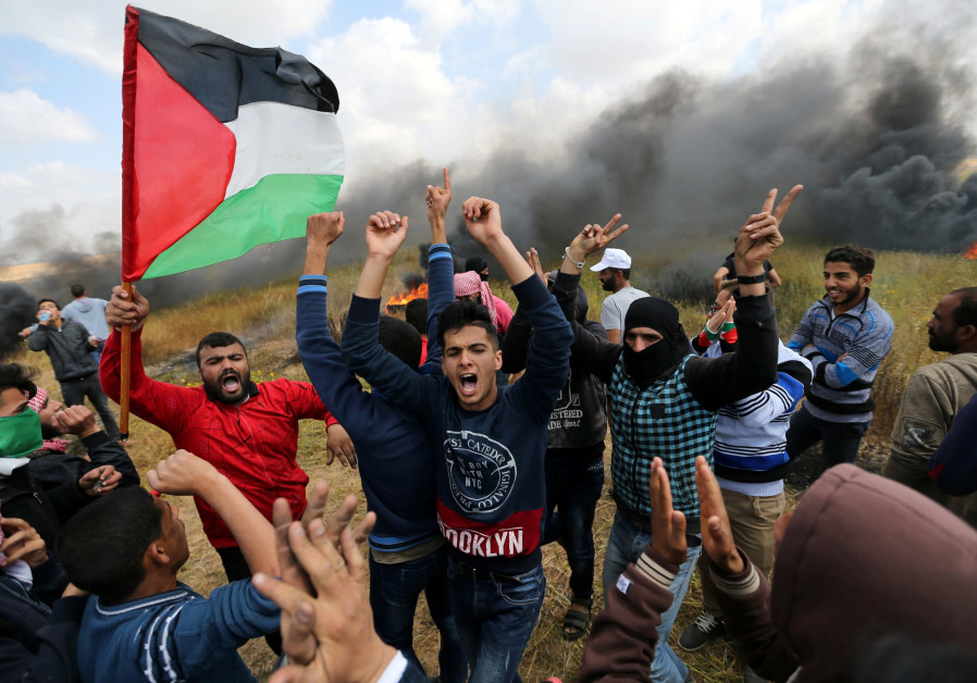 Palestinian protestors shout during clashes with the IDF ( IBRAHEEM ABU MUSTAFA / REUTERS).