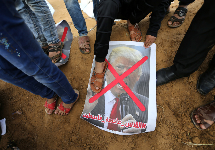 A Palestinian steps on a poster depicting US President Donald Trump during a tent city protest along the Israel border with Gaza, March 30, 2018 (IBRAHEEM ABU MUSTAFA / REUTERS)