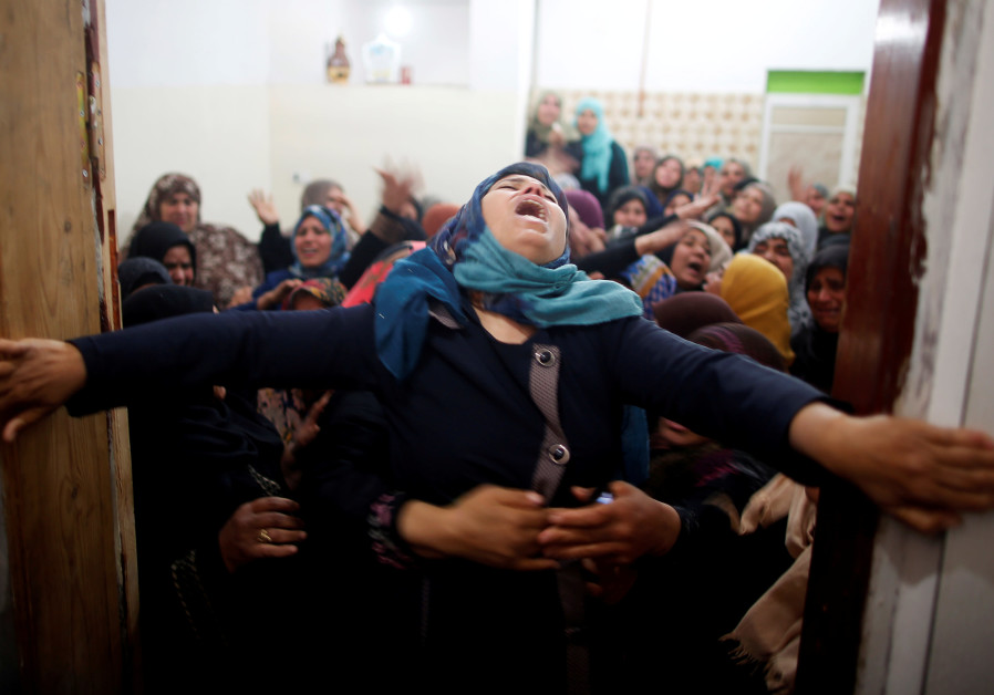Mourners hold back a relative of Palestinian Hamdan Abu Amshah, who was killed along Israel border with Gaza, during his funeral in Beit Hanoun town, in the northern Gaza Strip March 31, 2018 (SUHAIB SALEM / REUTERS).