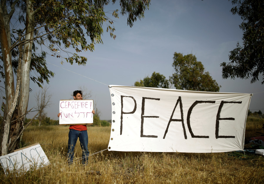 An Israeli peace activist holds a sign in front of the Israel-Gaza border, as Palestinians protest on the Gaza side of the border near Kibbutz Nahal Oz, Israel April 5, 2018 /  AMIR COHEN/REUTERS