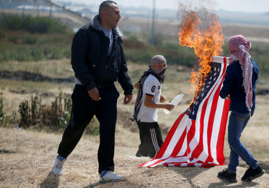Palestinians burn a U.S flag at the Israel-Gaza border during a protest demanding the right to return to their homeland, east of Gaza City April 6 / Mohammed Salem/ Reuters