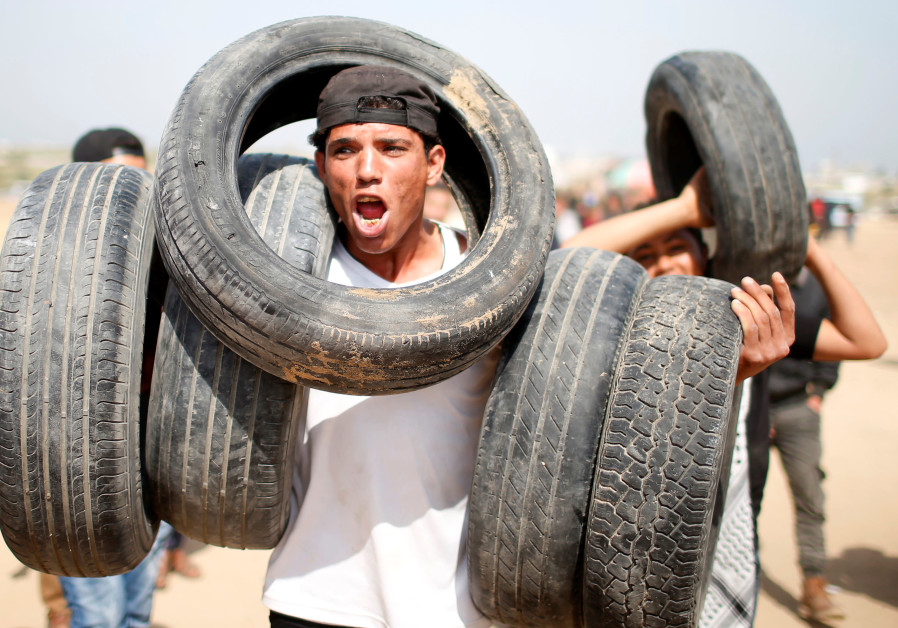 A Palestinian holds tyres at the Israel-Gaza border during a protest demanding the right to return to their homeland, east of Gaza City April 6, 2018 / MOHAMMED SALEM/ REUTERS