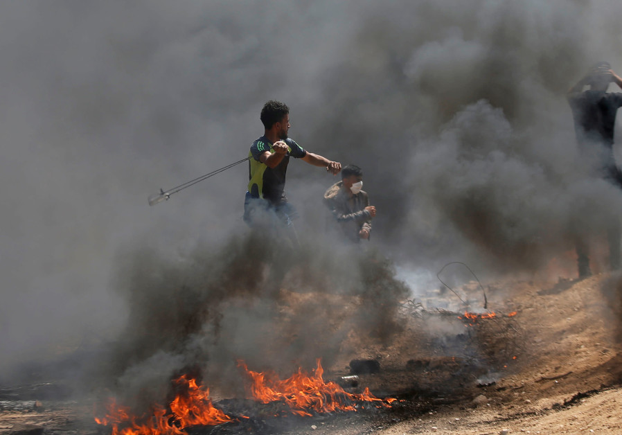 Palestinians throw rocks during protests in Gaza (credit: Mohammed Salem/ Reuters)