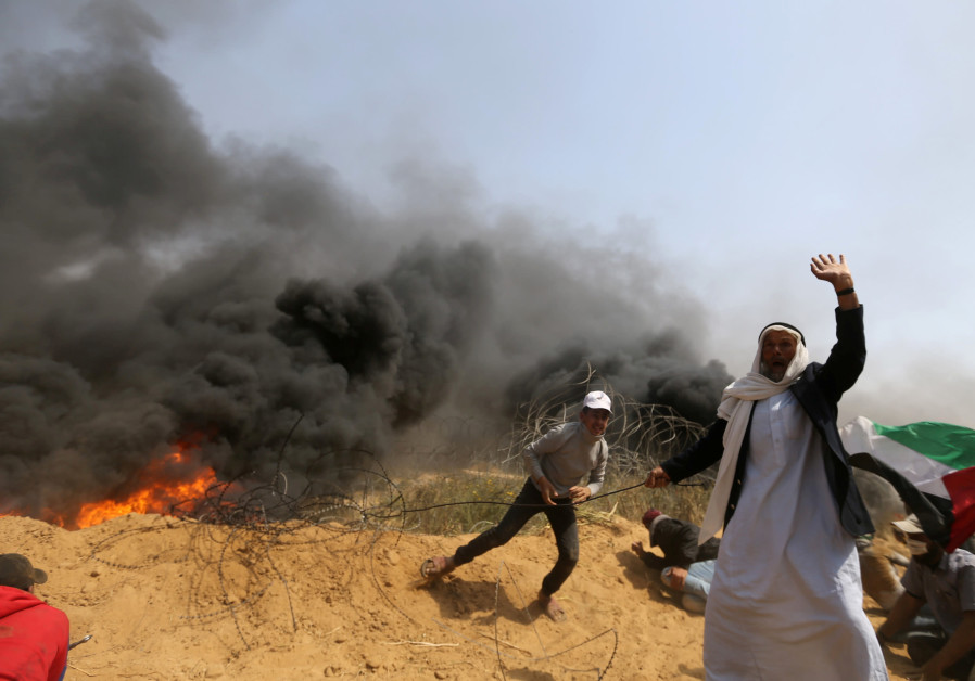 Palestinians remove a section of the border fence during Gaza protests (Ibraheem Abu Mustafa/ Reuters)