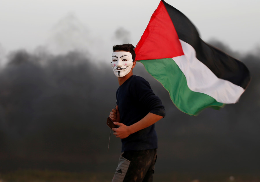 "A Gazan wears a Guy Fawkes mask and crries a Palestinian flag during the ""Great March of Return"" protests (credit: Mohammed Salem/ Reuters)"