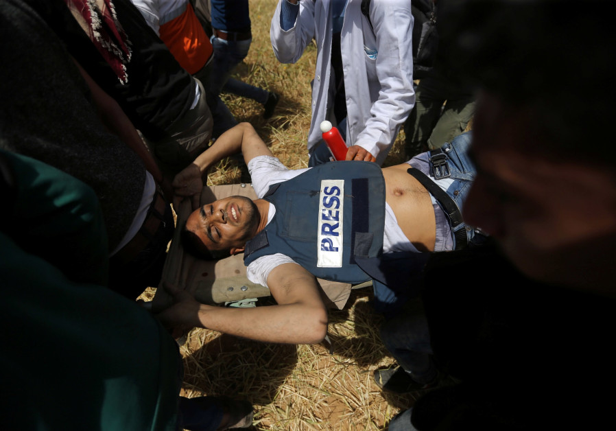 Palestinians aid an injured journalist during protests in Gaza (credit: Ibraheem Abu Mustafa/ Reuters)