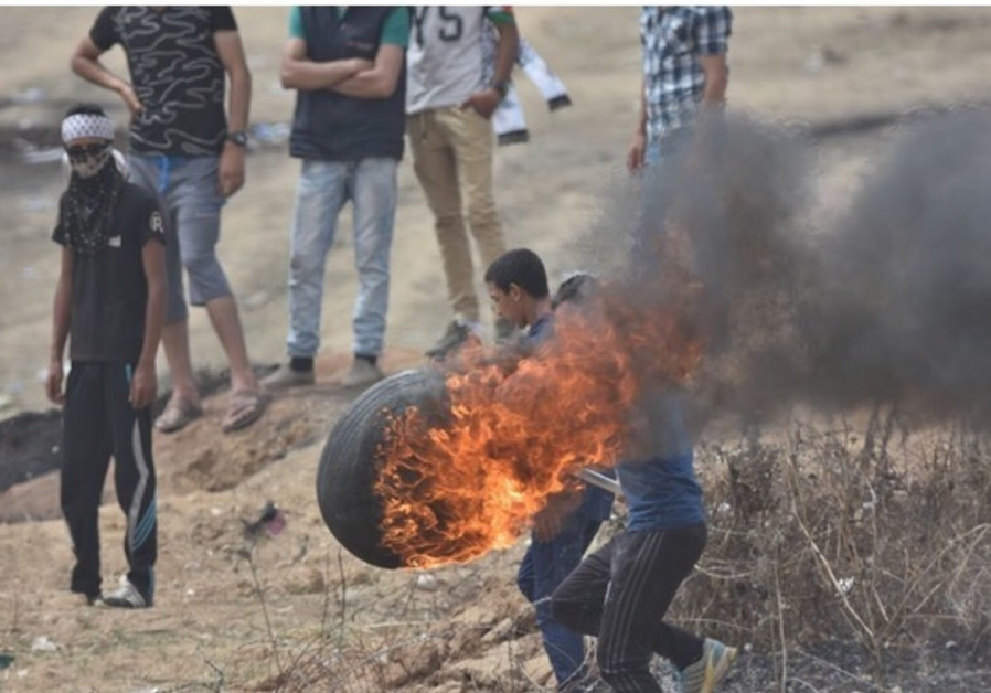 Palestinian protester with a burning tire / IDF SPOKESMAN'S UNIT