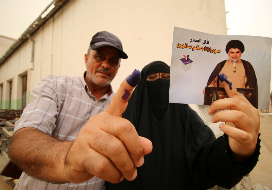 Iraqi people show their ink-stained fingers after casting their votes at a polling station during the parliamentary election in Basra, Iraq May 12, 2018. / ESSAM AL-SUDANI/ REUTERS