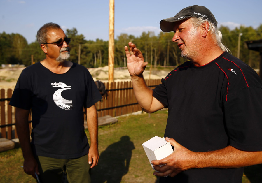 Archaeologists Yoram Haimi and Wojciech Mazurek (R) discuss in the perimeter of a Nazi death camp in Sobibor September 18, 2014. An archaeological dig, which has been carried out since 2007, has recently revealed the location of gas chambers under a road at the Sobibor death camp. KACPER PEMPEL / REUTERS
