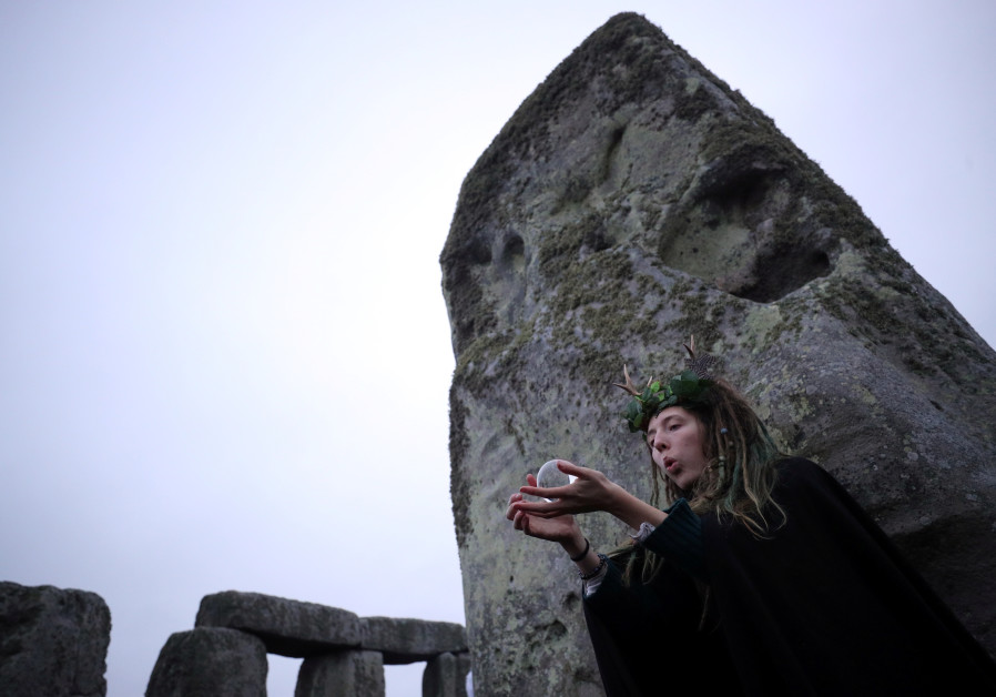 A reveller holds a crystal ball as the sun rises during the winter solstice at Stonehenge on Salisbury Plain in southern England, Britain, December 22, 2017. HANNAH MCKAY/ REUTERS