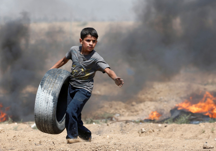 A Palestinian boy carries a tire during a protest marking al-Quds Day, (Jerusalem Day), at the Israel-Gaza border, east of Gaza City June 8, 2018.  MOHAMMED SALEM/ REUTERS
