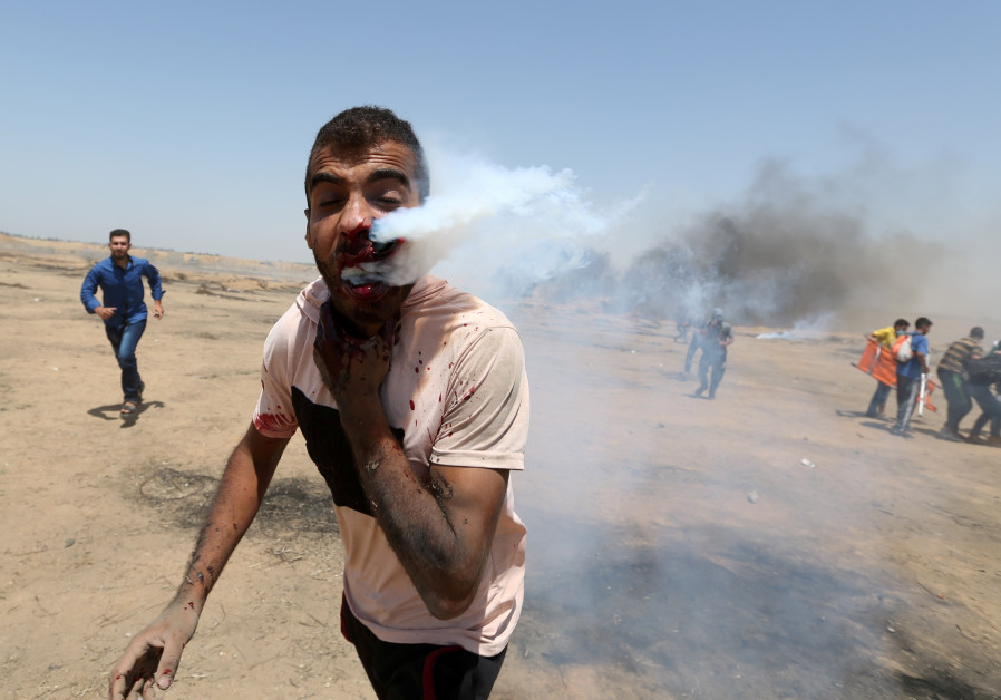 A wounded Palestinian demonstrator reacts as he is hit in the face with a tear gas canister fired by Israeli troops during a protest marking al-Quds Day, (Jerusalem Day), at the Israel-Gaza border in the southern Gaza Strip June 8, 2018.  IBRAHEEM ABU MUSTAFA / REUTERS