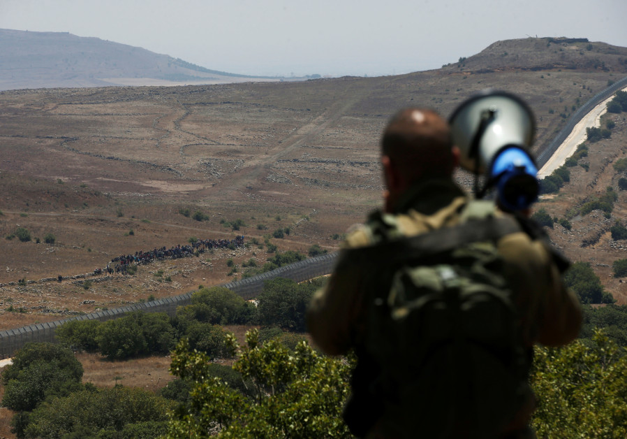An Israeli soldier speaks over a megaphone to people which stand next to the border fence between Israel and Syria from its Syrian side as it is seen from the Israeli-occupied Golan Heights near the Israeli Syrian border July 17, 2018. / RONEN ZVULUN / REUTERS