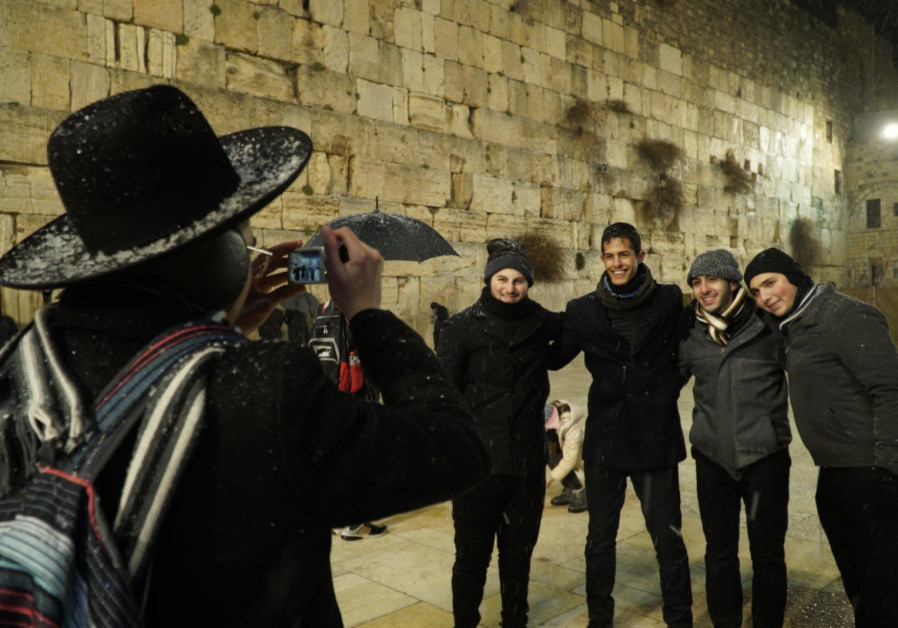 An orthodox Jew takes pictures of tourists at the Western Wall / MARC ISRAEL SELLEM