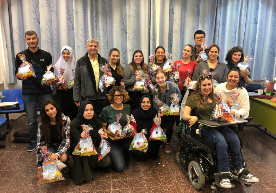 Students from an inter-faith dialogue course at Bar-Ilan University with Purim gift packages for needy families. (Courtesy)