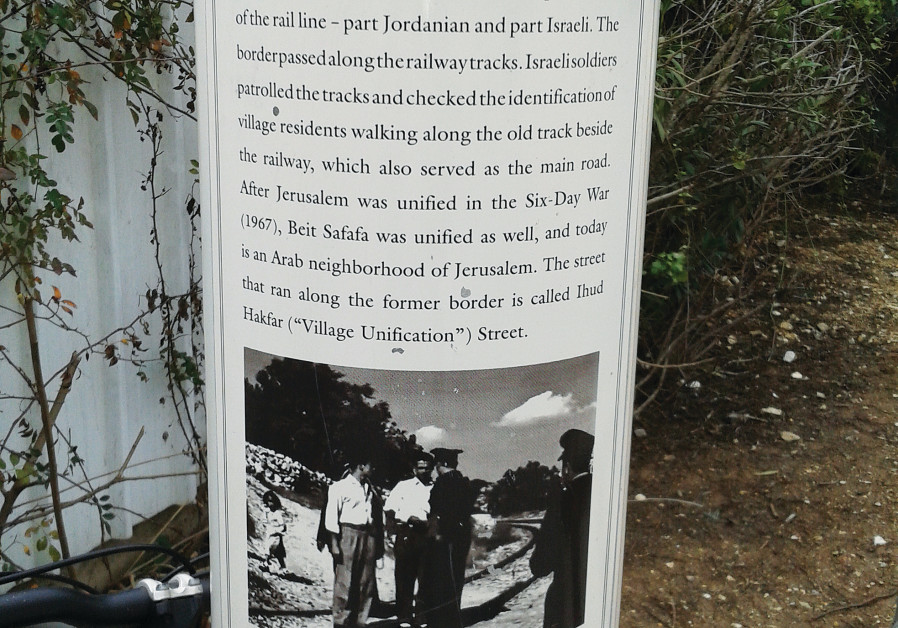 A sign along the old train tracks, now a bicycle path, explaining the division of Beit Safafa.
