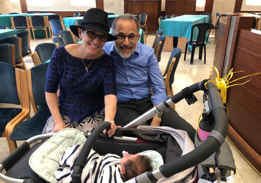 Beth and Paul White meet their new grandson at his brit milah early Thursday afternoon (Credit: Nefesh B'Nefesh)