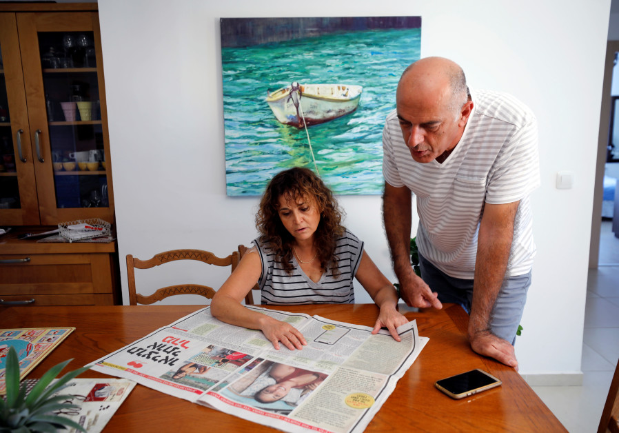 Israel, the uncle of Naama Issachar, and his wife look at a newspaper with an article about Naama at their home in Rehovot, Israel October 13, 2019 / AMIR COHEN/REUTERS