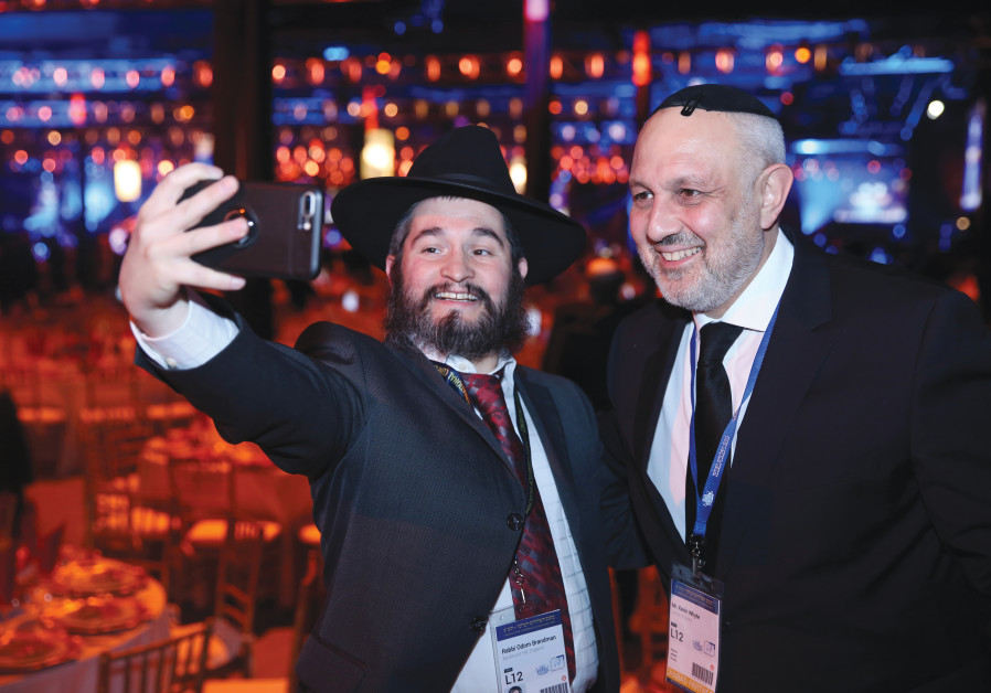 IMPACT OF technology: A Chabadnik snaps a selfie with a supporter at a New Jersey banquet in November 2019.  (Itzik Roytman/Chabad.org)