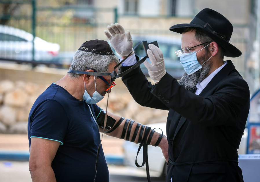 A CHABADNIK helps a man put on tefillin in Safed. (David Cohen/Flash90)