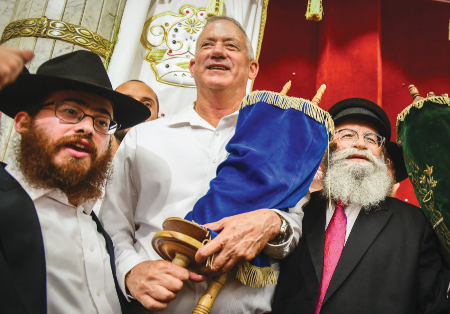 BLUE AND WHITE Party chairmen Benny Gantz carries a Torah scroll as he dances during Simhat Torah celebrations in Kfar Chabad in 2019. (Yossi Zeliger/Flash90)