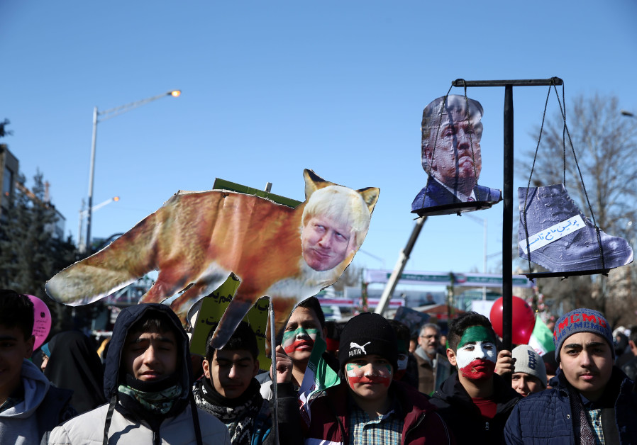 IRANIANS CARRY a cutout of US President Donald Trump and an image of British Prime Minister Boris Johnson during the commemoration of the 41st anniversary of the Islamic revolution in Tehran, on February 11. (Nazanin Tabatabaee/WANA via Reuters)
