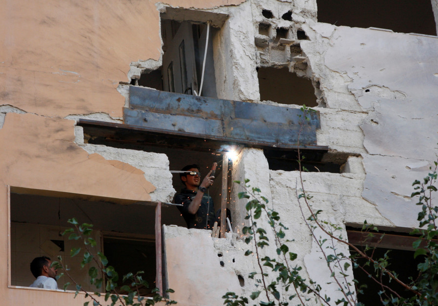 A WORKER fixes damage to a building from an Israeli airstrike in Damascus on November 20, 2019. Israel said it struck dozens of Iranian targets in Syria in response to rocket fire the prior day in the Golan Heights. (Omar Sanadiki/Reuters)