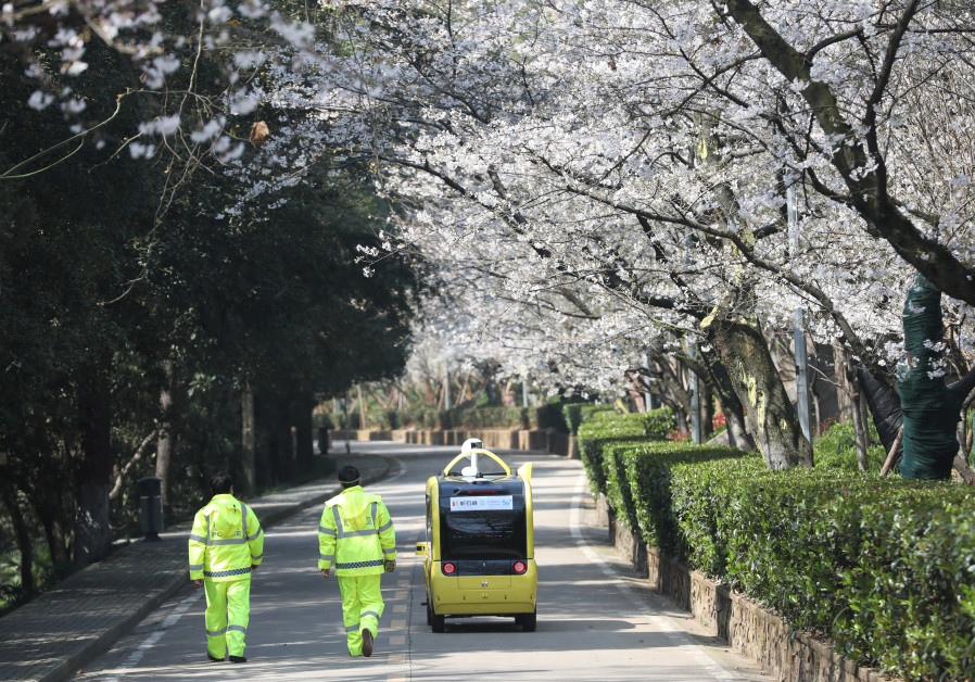 SECURITY PERSONNEL accompany a 5G-enabled autonomous vehicle, installed with a camera filming blooming cherry blossoms for an online live-streaming session, inside Wuhan University, Hubei province, China, on March 17. (China Daily via Reuters)