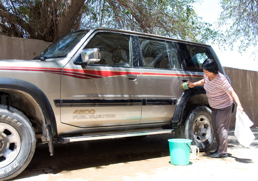 A MAID washes a car in front of her employers' house in Kuwait. (Gayle St. Claire/Reuters)